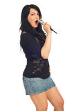 Elegant woman singing with microphone Royalty Free Stock Photo