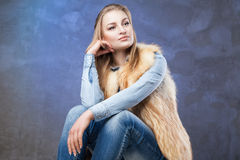 Elegant woman sits wearing blue jeans and fur vest Stock Photo