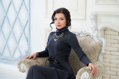 Elegant woman sitting on chair. Luxury Stock Photo