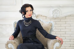 Elegant woman sitting on chair. Luxury Royalty Free Stock Image