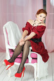 Elegant woman sitting on chair. Retro style. Red dress Stock Images