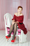 Elegant woman sitting on chair. Retro style. Red dress Royalty Free Stock Photo