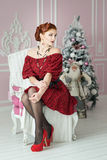 Elegant woman sitting on chair. Retro style. Red dress Royalty Free Stock Images