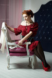 Elegant woman sitting on chair. Retro style. Red dress Stock Photography