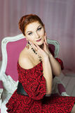 Elegant woman sitting on chair. Retro style. Red dress Royalty Free Stock Photography