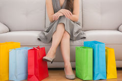 Elegant woman sitting on the couch with shopping bags Royalty Free Stock Photo