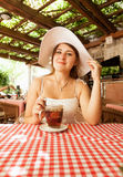 Elegant woman sitting with cup of tea at cafe Royalty Free Stock Image