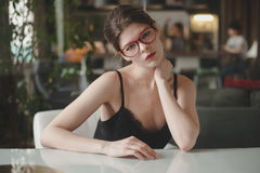 Elegant woman sitting at Desk in office. In a black dress and red glasses Stock Photo