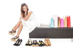 Elegant woman sitting next to shopping bags and pairs of shoes Royalty Free Stock Images