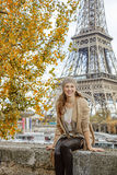 Elegant woman sitting on parapet on embankment near Eiffel tower Stock Images