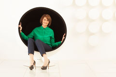Elegant woman sitting on spherical chair Stock Photos