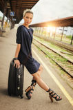 Elegant woman sitting on suitcases on the railway station Stock Photos