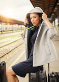 Elegant woman sitting on suitcases and waiting for the train stock image