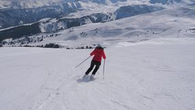 Sporty Woman Skier Carving Down The Slope In The Mountains Ski Resort At Winter. Elegant woman skier in a red jacket and black trousers skis on the slope alone stock video footage
