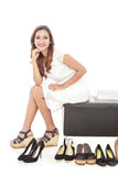 Elegant woman smiling and sitting next to pairs of shoes Royalty Free Stock Photo