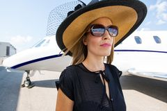 Elegant Woman Standing Against Private Jet Royalty Free Stock Image