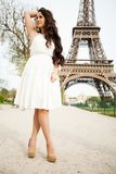 Elegant woman standing in a park with Eiffel Tower on the background Royalty Free Stock Images
