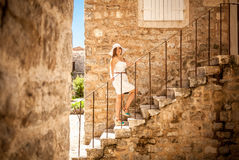 Elegant woman standing on stone stairs at old street Royalty Free Stock Images