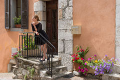 Elegant woman stands on the porch of the house. Royalty Free Stock Images