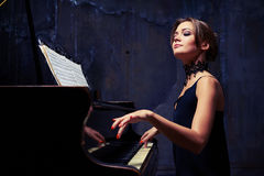 Elegant woman starts piano performance while sitting isolated in Royalty Free Stock Photo