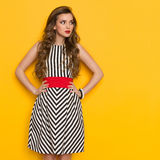 Elegant Woman In Striped Dress Glances Sideways. Beautiful young woman in black and white striped dress posing with hands on hip and looking away. Three quarter Stock Image