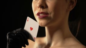 Elegant woman stroking her face with ace of hearts, fortune sign, gambling. Stock footage stock video