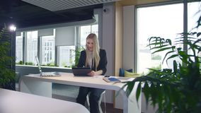 Stylish business woman with tablet in office. Elegant woman in suit sitting at table with laptop and surfing tablet in. Elegant woman in suit sitting at table stock video