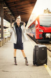 Elegant woman with suitcase posing on the railway station Royalty Free Stock Photos