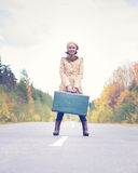 Elegant woman with a suitcase traveling the Royalty Free Stock Photography