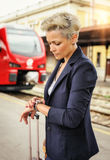 Elegant woman with suitcase waiting a train at the railway stati Royalty Free Stock Photography