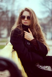 Elegant woman in sunglasses on the bench Royalty Free Stock Photo