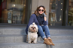 Elegant woman in sunglasses with shih-tzu dog sitting on the steps Royalty Free Stock Images