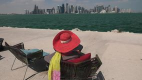 Woman relaxing in Qatar. Elegant woman with sunhat looking the view of Doha Bay in a sunny day. Lifestyle caucasian tourist enjoys skyscrapers of Doha Downtown stock footage