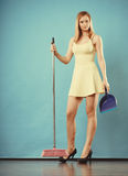 Elegant woman sweeping floor with broom Royalty Free Stock Image
