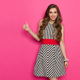 Elegant Woman Thumb Up. Smiling attractive woman in black and white striped dress showing thumb up and looking at camera, Three quarter length studio shot on Royalty Free Stock Photo