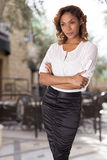 Elegant woman in tight black skirt stands with arms crossed. Stock Photography