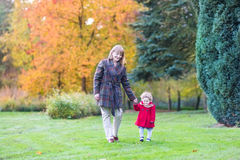 Elegant woman with toddler girl in autumn park Royalty Free Stock Images