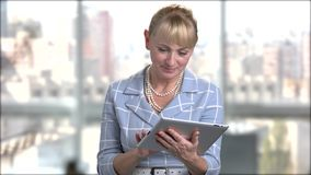 Elegant woman using digital tablet. Pretty mature woman working on pc tablet on window city background. People, technology and lifestyle stock footage