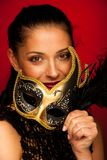 Elegant woman with venice mask over stilish red background - car. Nival Royalty Free Stock Photo