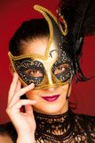 Elegant woman with venice mask over stilish red background - car. Nival Royalty Free Stock Photography