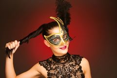 Elegant woman with venice mask over stilish red background - car. Nival Stock Photo