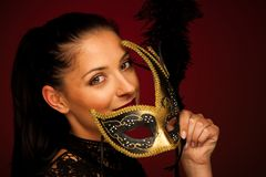 Elegant woman with venice mask over stilish red background - car. Nival Stock Image