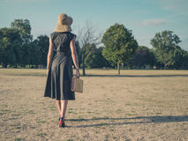 Elegant woman walking in park with briefcase Royalty Free Stock Images