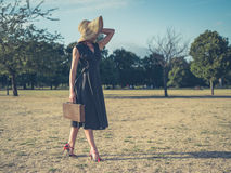 Elegant woman walking in park with briefcase Stock Photo