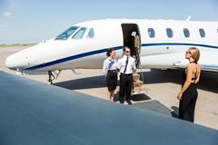 Elegant Woman Walking Towards Private Jet. Elegant women walking towards private jet while pilot and stewardess standing at airport terminal Stock Photos