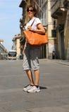 Elegant woman walks through the streets of a European city with. Elegant young woman walks through the streets of a European city with the big leather bag Stock Photos