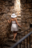 Elegant woman wearing big hat exploring ancient stone castle Stock Image