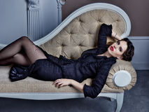Elegant woman wearing black suit liyng on sofa. Fashion style portrait Royalty Free Stock Images
