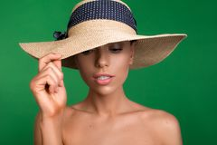 Elegant woman wearing summer accessory. Portrait of well cared young girl touching hat on her head and looking down. Isolated on background Royalty Free Stock Images