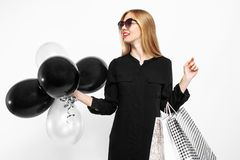 Elegant woman wearing sunglasses in a black dress and red lips, stock photography